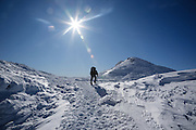 A hiker on the Appalachian Trail (Crawford path) in the Presidential Range of the White Mountains, New Hampshire USA during the winter months. Mount Monroe is in the background.