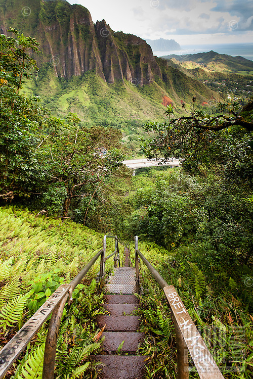 """An aerial view at dawn of the Ko'olau mountain range and H-3 Freeway with steps descending into Haiku valley from the Haiku Stairs (""""Stairway to Heaven"""") hiking trail in Kaneohe, O'ahu"""