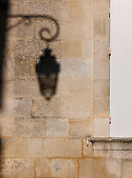 The shadow of a traditional street lamp in Saint Emilion, France