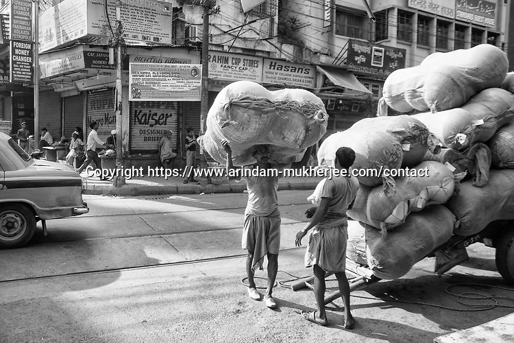 Daily wage laborer carry heavy goods on their head in Kolkata, India.
