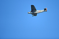 A Ford Trimotor C4A military transport plane flies over an Erie Seawolves game against the Harrisburg Senators on July 2, 2013 at Jerry Uht Park in Erie, Pennsylvania.  Erie defeated Harrisburg 2-1.  (Mike Janes/Four Seam Images)