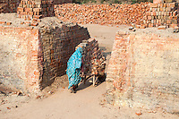 Rajasthan, India.  Woman Pushing a Wheelbarrow of Bricks to a Location to Await Transport to Market.