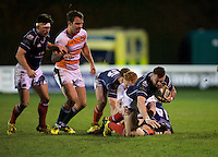 Rory Hughes of London Scottish Football Club is tackled during the Greene King IPA Championship match between London Scottish Football Club and Ealing Trailfinders at Richmond Athletic Ground, Richmond, United Kingdom on 26 December 2015. Photo by Alan  Stanford / PRiME Media Images
