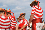 Venice Italy 2009. GROUP OF SENIOR  GONDOLIERS WEARING TRADITIONAL RED AND WHITE STRIPPED SHIRTS AND STRAW HATS