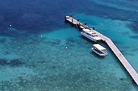 Two boats anchored next to a wooden pier in tranquil waters, Amedee Island, New Caledonia.