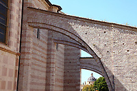 """Assisi: The ancient Santa Chiara church is characterized both by the alternance of white and rose-colored bricks and by the series of half arcs on one of its sides. Here, a close view of these last ones. The dome of another church of the town, surrounded by them, """"Chiesa Nuova"""" (the New Church) is visible on the background."""