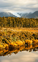 Sunset over Five Mile Lagoon with Franz Josef Glacier visible under clouds, Westland Tai Poutini National Park, West Coast, UNESCO World Heritage Area, South Westland, New Zealand, NZ