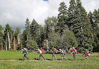 Photo story of Philmont Scout Ranch in Cimarron, New Mexico, taken during a Boy Scout Troop backpack trip in the summer of 2013. Photo is part of a comprehensive picture package which shows in-depth photography of a BSA Ventures crew on a trek.  In this photo BSA Venture Crew Scouts make their way across a trail against the backdrop of the mountains in the backcountry at Philmont Scout Ranch.   <br /> <br /> The  Photo by travel photograph: PatrickschneiderPhoto.com