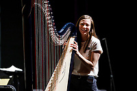 USA International Harp Competition Executive Director Erin Brooker-Miller moves a harp off stage during an orchestra rehearsal for the Final Stage concert at the 11th USA International Harp Competition at Indiana University in Bloomington, Indiana on Friday, July 12, 2019. (Photo by James Brosher)