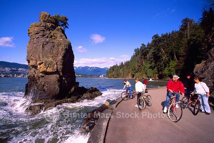 Stanley Park, Vancouver, BC, British Columbia, Canada - Cyclists stopping on Seawall at Siwash Rock along English Bay