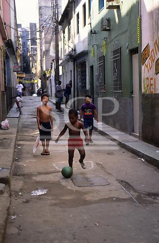 Rio de Janeiro, Brazil. Boys playing football on the street in shanty town.