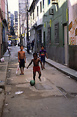 Rio de Janeiro, Brazil. Boys playing football on the street in shanty town.