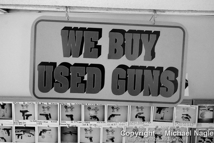 BRONX  --  SEPTEMBER 25, 2003:  A sign reading 'we buy used guns' hangs from the ceiling above a corkboard tiled with poloraid photos of illegal guns bought in 2003 in the Manhattan office of the NYPD Firearms Investigation Unit, on September 25, 2003, in the Bronx.  The Unit bought over 486 guns off of the streets in 2002.  (PHOTOGRAPH BY MICHAEL NAGLE).
