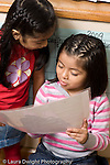Education Preschool 3-5 year olds two girls looking at sign or illustration vertical