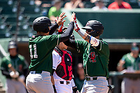 Great Lakes Loons outfielder Andy Pages (44) is greeted at the plate by teammate Miguel Vargas (11) after a home run on May 30, 2021 against the Lansing Lugnuts at Jackson Field in Lansing, Michigan. (Andrew Woolley/Four Seam Images)