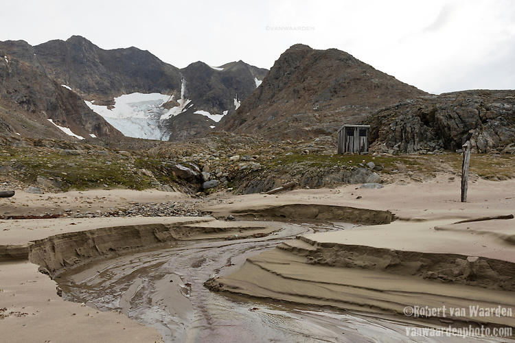 An abanonded hut sits lonely on a beach on Greenland's east coast. In the background, a receding glacier caused by climate change.