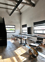 A functional, industrial space with exposed roof beams and a wood floor. An Eames recliner stands next to long black table and light wood chairs.
