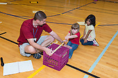 MR / Schenectady, NY. Zoller Elementary School (urban public school). Kindergarten inclusion classroom. Gym teacher helps student hold his knees down as student uses teacher-made equipment to test student flexibility. This is part of his students' yearly assessment of their physical education skills. MR: Mel16, Bin1, Ram13. ID: AM-gKw. © Ellen B. Senisi.