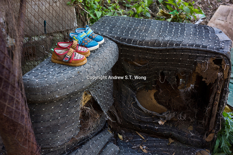 """The shoes of children of jobless tin miners are seen outside their quarters at a tin mine in Gejiu, November 2014. Gejiu in Yunnan province is a """"Tin Centre"""" with more than 2,000 years of mining history. Tin articles made in Gejiu are highly acclaimed in China. However, the tin mining and related industries are in decline."""