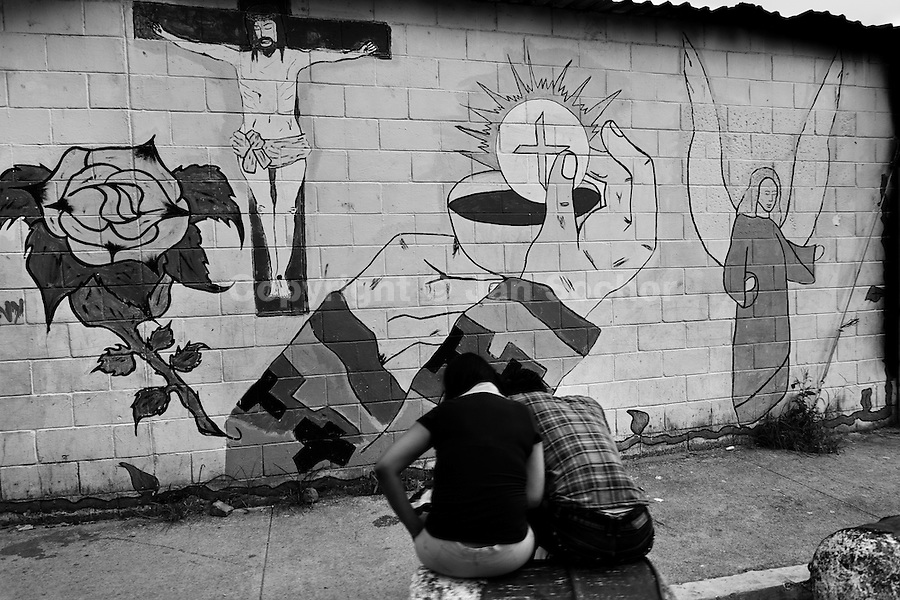 Young people sit in front of the religious murals painted on the wall in the gang neighborhood in San Salvador, El Salvador, 19 May 2011. During the last two decades, Central America has become the deadliest region in the world that is not at war. According to the UN statistics, more people per capita were killed in El Salvador than in Iraq, in recent years. Due to the criminal activities of Mara Salvatrucha (MS-13) and 18th Street Gang (M-18), the two major street gangs in El Salvador, the country has fallen into the spiral of fear, violence and death. Thousands of Mara gang members, both on the streets or in the overcrowded prisons, organize and run extortions, distribution of drugs and kidnappings. Tattooed armed young men, mainly from the poorest neighborhoods, fight unmerciful turf battles with their coevals from the rival gang, balancing between life and death every day. Twenty years after the devastating civil war, a social war has paralyzed the nation of El Salvador.