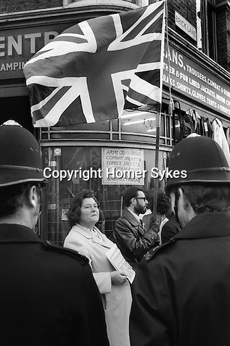 National Front supporters sell the National Front News, every Sunday morning at the junction of Brick Lane and Bethnal Green Road. London 1970s. There was a regular stand off, with police and Socialist Workers Party members selling their weekly newspaper...