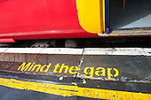 "London England. Colourful South West train and platform with ""Mind the Gap"" in yellow."