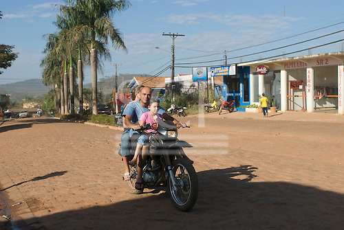Pará State, Brazil. The town of Tucumã; mother, father and daughter on a motorbike.