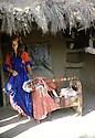 Iraq 1985   Young woman with her baby in a cradle in front of her home in the district of Lolan    Irak 1985   Devant une maison, une  jeune femme a coté du berceau de son enfant dans la region de Lolan