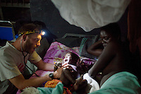 Dr. Eamonn Vitt  examines Innocent Oyem. His mother is HIV positive. He was being treated for malaria. At the time of his treatment, his status was not yet determined..Madi Opei IDP Camp, Kitgum District, Uganda, November 2 2009..