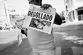 """Nuevo Laredo, Mexico<br /> June 7, 2007<br /> <br /> In Nuevo Laredo, a United States border town, street vendors sell a  paper displaying the days regional drug related execution with the headline, """"Cut Throat"""". Drug related executions in the Nuevo Laredo are a daily event."""
