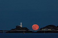 A May super moon, known also as a flower moon is seen rising over Mumbles Lighthouse near Swansea, Wales, UK. Wednesday 26 May 2021
