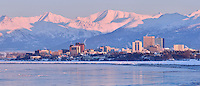 The setting sun turns Anchorage, Alaska and the Chugach Mountains pink on a bitterly cold winter day.