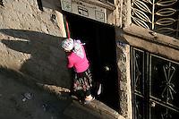 Girl hanging out of doorway in Mardin, southeastern Turkey