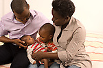two year old toddler boy with parents mother and father with newborn 3 week old baby brother vertical