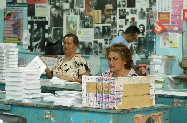 """Duckereikollektiv in Caracas<br /> Das Druckereikollektiv """"Instituto Municipal de Publicaciones"""" wurde 2003 von linken Arbeiterinnen und Arbeitern gegruendet. Schon drei Jahre zuvor, 2000, war die Druckerei von einigen sozialen Aktivisten uebernommen worden. Damals hatte die Druckerei absolut unwirtschaftlich und zu schlechten Bedingungen fuer die Arbeiterinnen und Arbeiter mit 160 Beschaeftigten produziert. Heute arbeiten hier ca. 250 Frauen und Maenner, die gute Auftragslage erfordert inzwischen ein Dreischichtsystem mit je 7 Stunden inclusive Pausen. Die Werksleitung muss genauso wie die Arbeiter an bei jeder Schicht anwesend sein.<br /> Die Druckerei stellt Publiaktionen fuer linke Gruppen, Stadtteilgruppen im ganzen Land und die Stadtverwaltung von Caracas her.<br /> Auf dem Firmengelaede wurde zur medizinischen Versorgung des Stadtteils eine Station des Gesundheitsprogrammes """"Barrio Adentro"""" eingerichtet. Hier gibt es kostenlos u.a. zahnaerztliche und gynokologische Versorgung.<br /> Hier: Frauen sortieren Druckerzeugnisse zu Vorbereitung fuer die Buchbinderei.<br /> 8.11.2004, Caracas / Venezuela<br /> Copyright: Christian-Ditsch.de<br /> [Inhaltsveraendernde Manipulation des Fotos nur nach ausdruecklicher Genehmigung des Fotografen. Vereinbarungen ueber Abtretung von Persoenlichkeitsrechten/Model Release der abgebildeten Person/Personen liegen nicht vor. NO MODEL RELEASE! Nur fuer Redaktionelle Zwecke. Don't publish without copyright Christian-Ditsch.de, Veroeffentlichung nur mit Fotografennennung, sowie gegen Honorar, MwSt. und Beleg. Konto: I N G - D i B a, IBAN DE58500105175400192269, BIC INGDDEFFXXX, Kontakt: post@christian-ditsch.de<br /> Bei der Bearbeitung der Dateiinformationen darf die Urheberkennzeichnung in den EXIF- und  IPTC-Daten nicht entfernt werden, diese sind in digitalen Medien nach §95c UrhG rechtlich geschuetzt. Der Urhebervermerk wird gemaess §13 UrhG verlangt.]"""