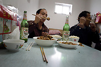 CHINA. Beijing. A migrant worker family eat together  in Lao San Yu Village (a migrant worker village) in the southern district, Daxing. 2010
