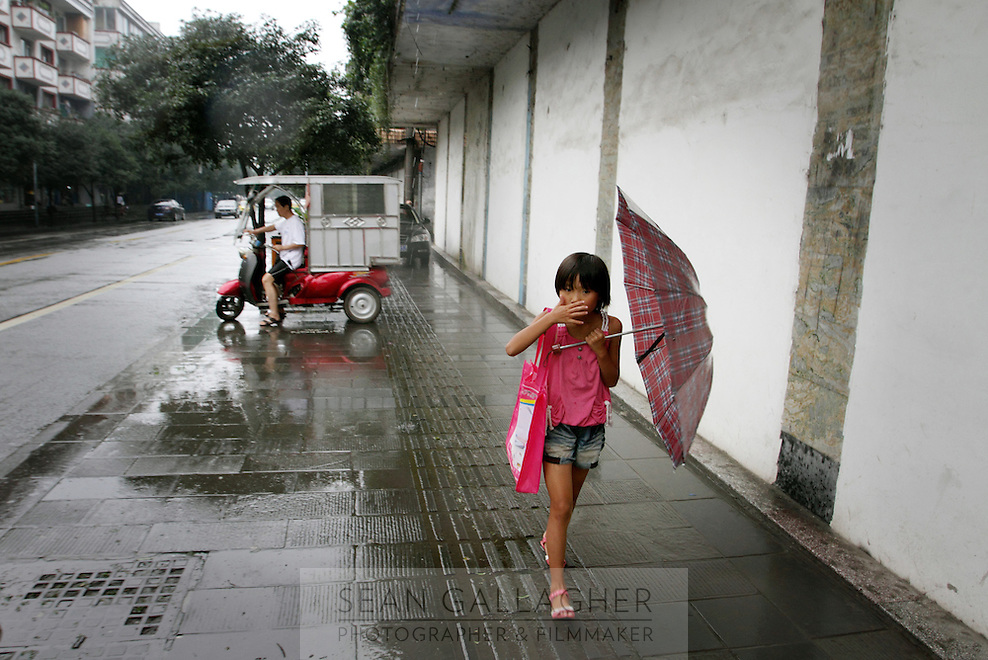 """A young girl in the town of Dujiangyan, famed for its ancient irrigation System. The system is regarded as an """"ancient Chinese engineering marvel."""" By naturally channeling water from the Min River during times of flood, the irrigation system served to protect the local area from flooding and provide water to the Chengdu basin. Sichuan Province. 2010"""