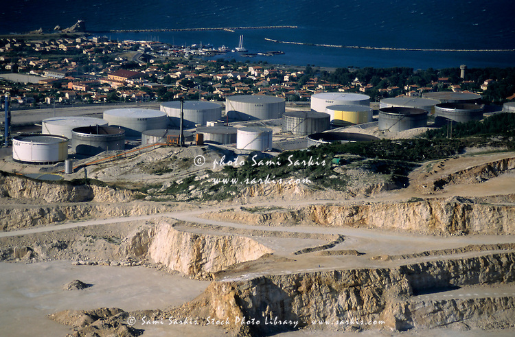 Oil tanks and stone quarry near sea.