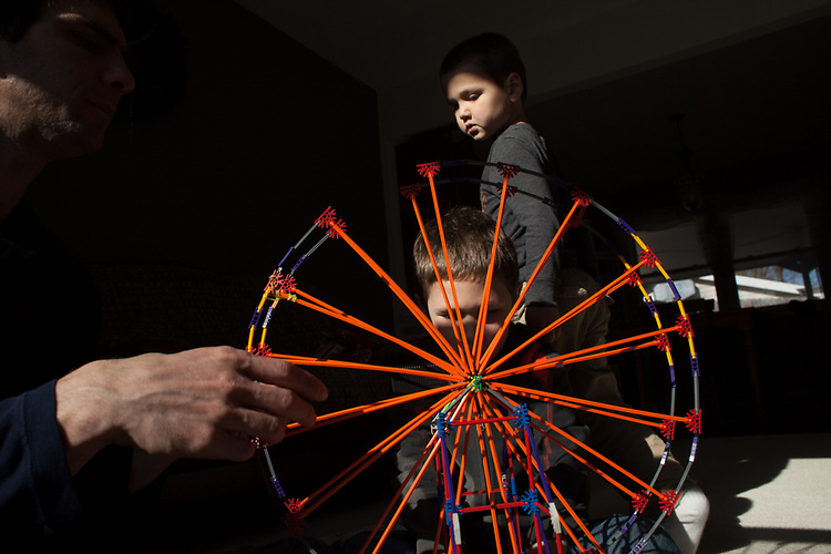 The boys pooled their money to buy a garage sale motorized ferris wheel, which needed a lot of input from Dad to put together.