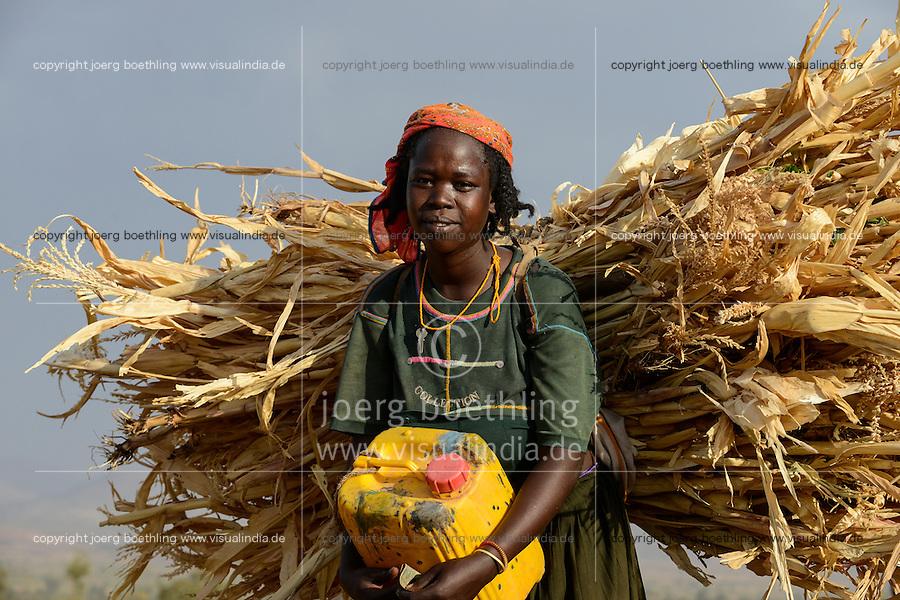 ETHIOPIA, Southern Nations, Lower Omo valley, tribal woman carry maize straw / AETHIOPIEN, Unteres Omo Tal, Frau einer indigenen Volksgruppe, traegt Maisstroh