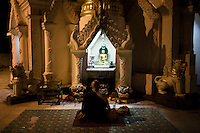 A monk sits and prays at the Maha Gandha Bell temple on the western side of the Shwedagon Pagoda.