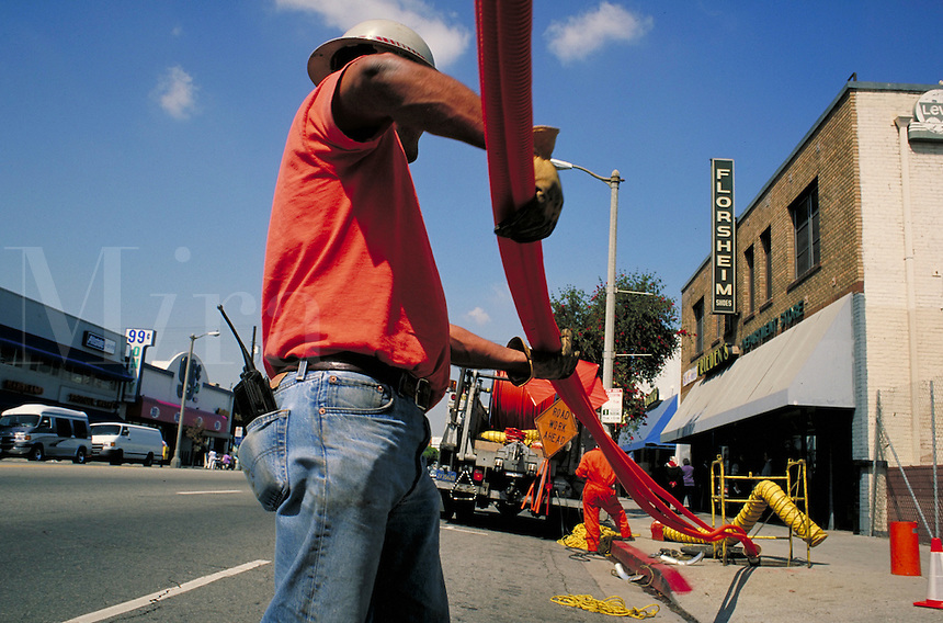 Underground fiber optic cable conduit installation in business district right of way, Los Angeles, CA. Communications, job, career, blue collar worker. Hard hat worker. Los Angeles California.