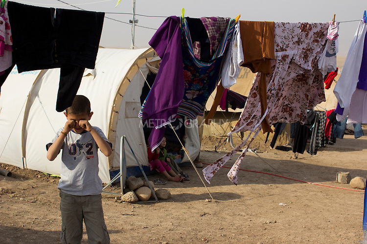 DOMIZ, IRAQ: A Syrian refugee rubs dust from his eyes outside his tent in the Domiz refugee camp in the Kurdish region of northern Iraq...The semi-autonomous region of Iraqi Kurdistan has accepted around 60,000 refugees from war-torn Syria. Around 20,000 refugees live in the Domiz camp which sits 60 km from the Iraq-Syria border...Photo by Younes Mohammad/Metrography