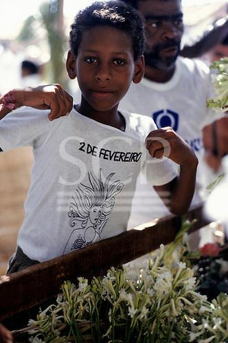 Salvador, Bahia, Brazil. Boy wearing a t-shirt showing Iemanja and the date 2 February; Festival of Iemanja.