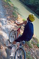 Young boy biking, Carcassonne, Canal du Midi, France.