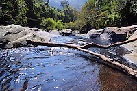 Lake and waterfall cascades in mountains among huge stones and jungle forest