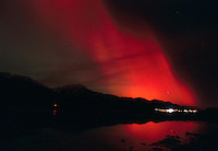 Intense red northern lights flare over the Tongass National Forest with lights of Douglas showing.