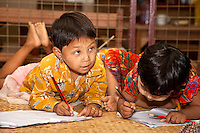 Myanmar, Burma. Bagan.  Young Burmese Girls Writing in their Notebooks.  One has thanaka paste, a cosmetic sunscreen, on her face.