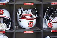 An North Carolina State Wolfpack batting helmet sits in a rack in the dugout following the game against the Army Black Knights at Doak Field at Dail Park on June 3, 2018 in Raleigh, North Carolina. The Wolfpack defeated the Black Knights 11-1. (Brian Westerholt/Four Seam Images)