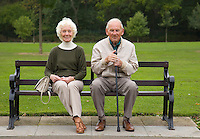 Elderly couple relax on park bench. England.